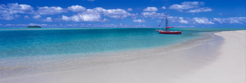Red sail boat floating in the turquoise ocean just off a white sand beach in the Great Barrier Reef of Australia