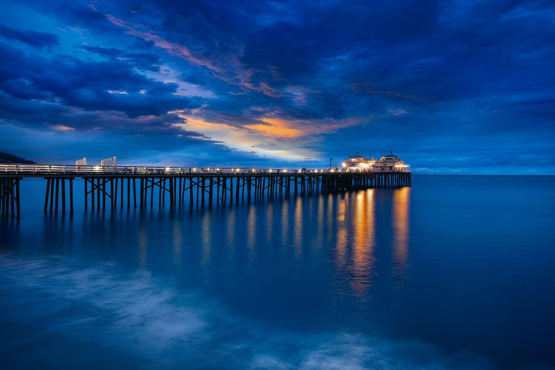 Malibu Pier leading out over the ocean in California lit up at night under a cloud filled sky