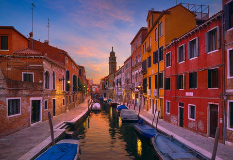 Boat filled canal surrounded by old buildings and a bell tower in Venice Italy at sunrise