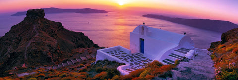 White plastered church and courtyard on a rock cliff overlooking the ocean off Santorini Greece