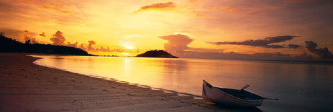 White row boat on the sand of Lizard Island Beach, Australia at sunset