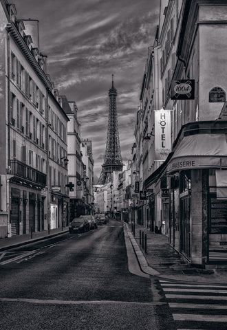 Black and white city street in Paris France with cars and buildings in front of the Eiffel Tower and a cloud filled sky