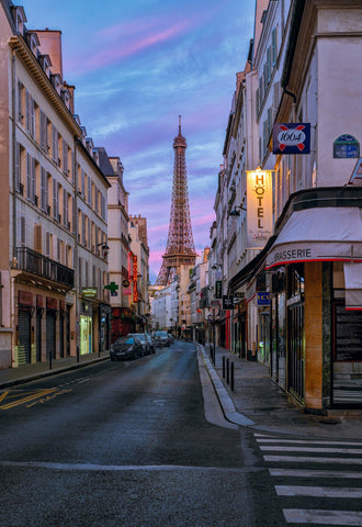 City street in Paris France with cars and white buildings in front of the Eiffel Tower and a pink cloudy sky