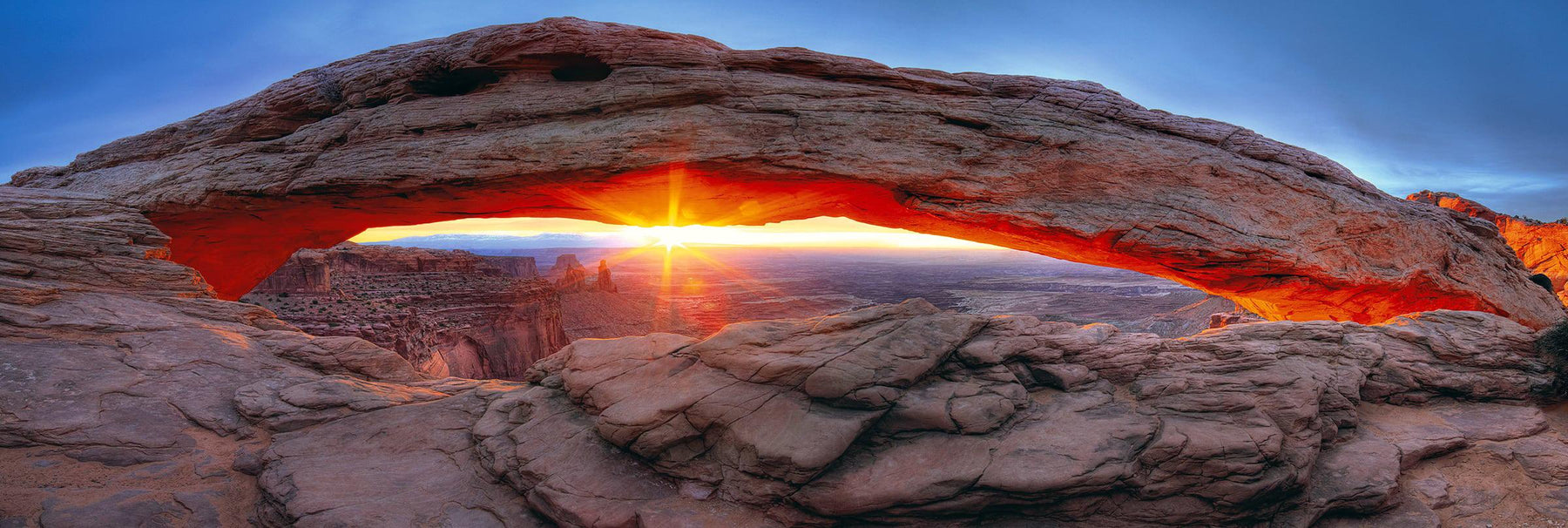 Sunburst shining through the stone arch and onto the rock valley of Canyonlands National Park Utah
