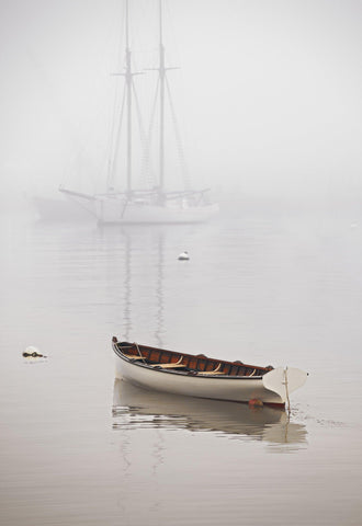 Row boat and sail boat floating in a fog filled harbor in Martha's Vineyard Massachusetts