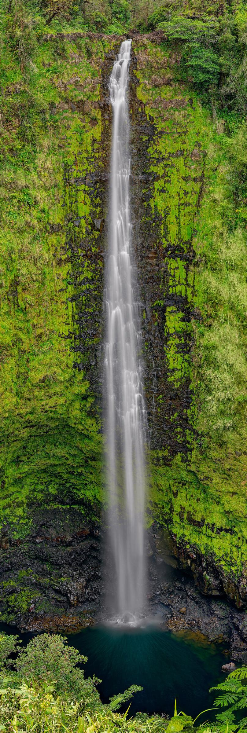Waterfall pouring down a tall moss covered black rock cliff into a water hole below
