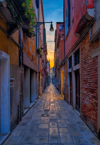 Stone brick alley leading through the old buildings of Prague Czech Republic at sunset