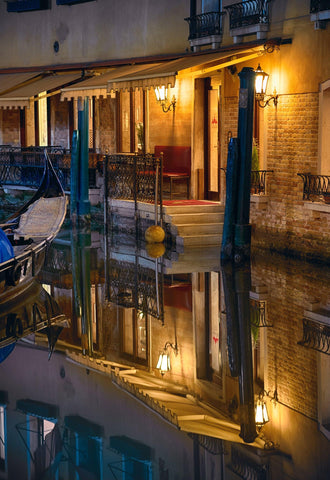 Boat near the back porch of an old building reflecting off the canal in Venice Italy at night