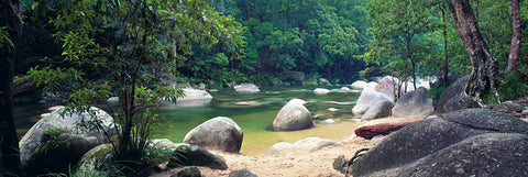 Rock and sand shore of the river running through the tropical rainforest of Mossman Gorge Australia