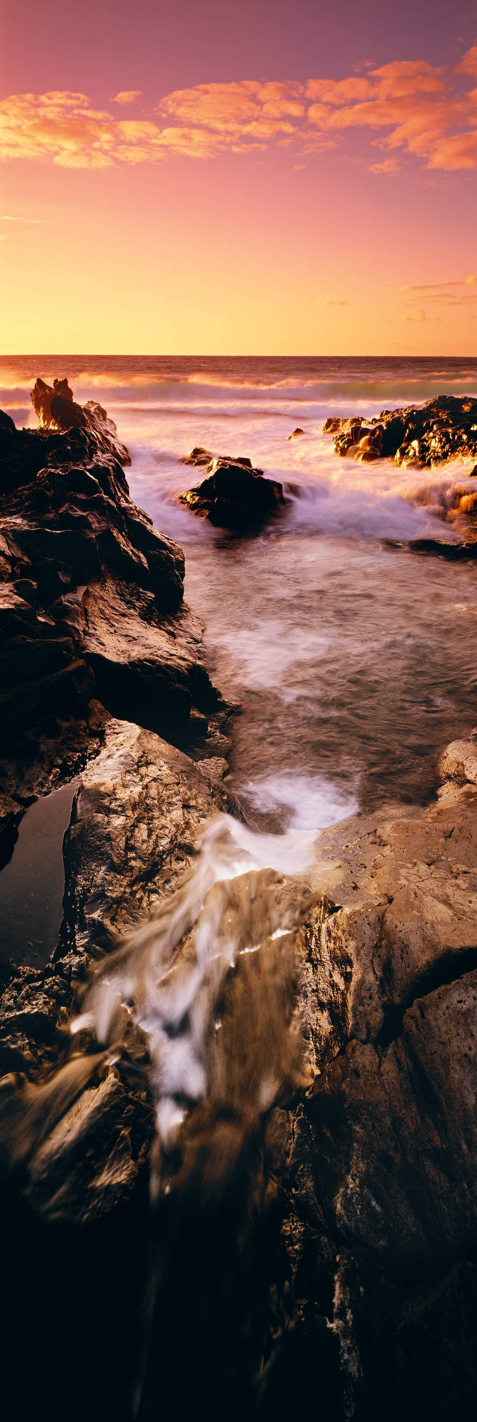 Ocean waves washing over the rocky tidal pools in Hana Hawaii at sunset