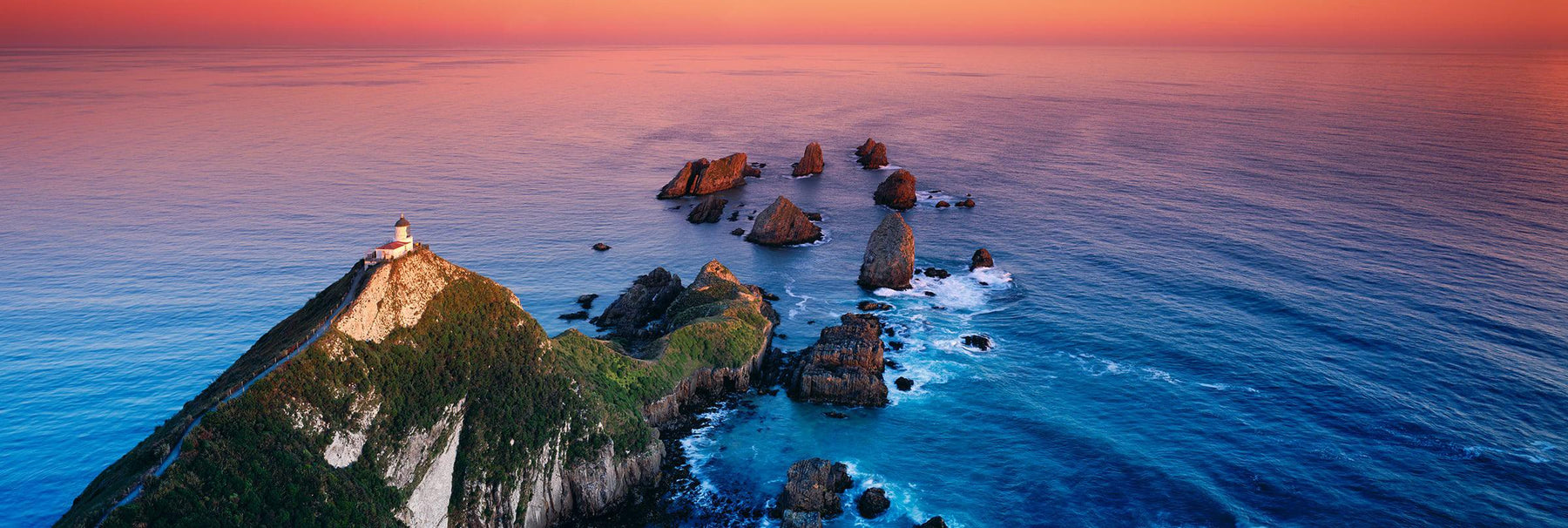 View looking down on Nugget Point Lighthouse that sits on a cliff overlooking the Catlins coast in New Zealand