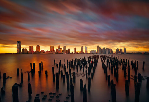 Wood pilons in the bay across from a New York skyline with blurred clouds overhead