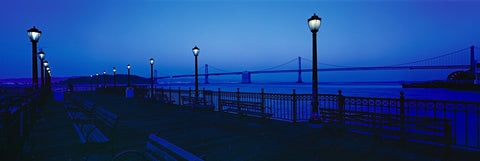 Wooden pier with antique lamp posts and benches at night in the San Francisco Bay