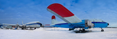 Two old airplanes sitting in a snow covered field in Fairbanks Alaska