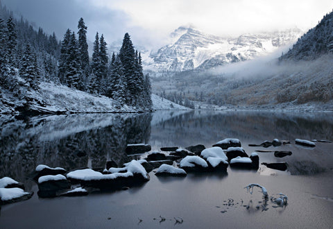 Snow covered rocks in Lake Maroon with a pine tree forest and snow peaks of Maroon Bells Colorado