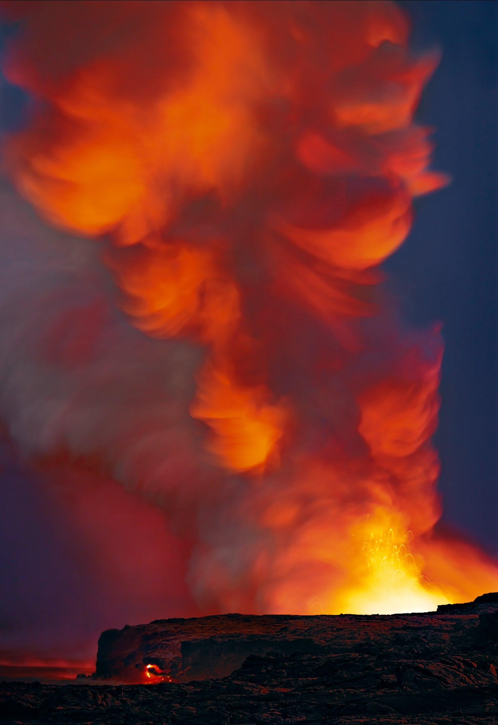 Explosion of fire creating a cloud of smoke on the black lava field shoreline of Kilauea Hawaii