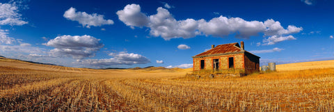 Sandstone shack in a cut wheat field in the outback of Burra Australia with puffy white clouds overhead in a blue sky