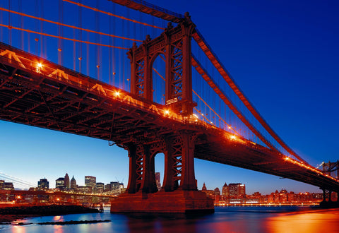 Manhattan Bridge lit up at night from the waters edge with New York City in the background