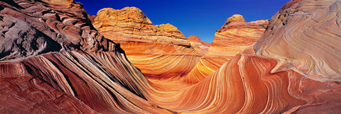 Orange and brown wave like rock formations in the slickrock hills of Vermillion Cliffs National Park Arizona