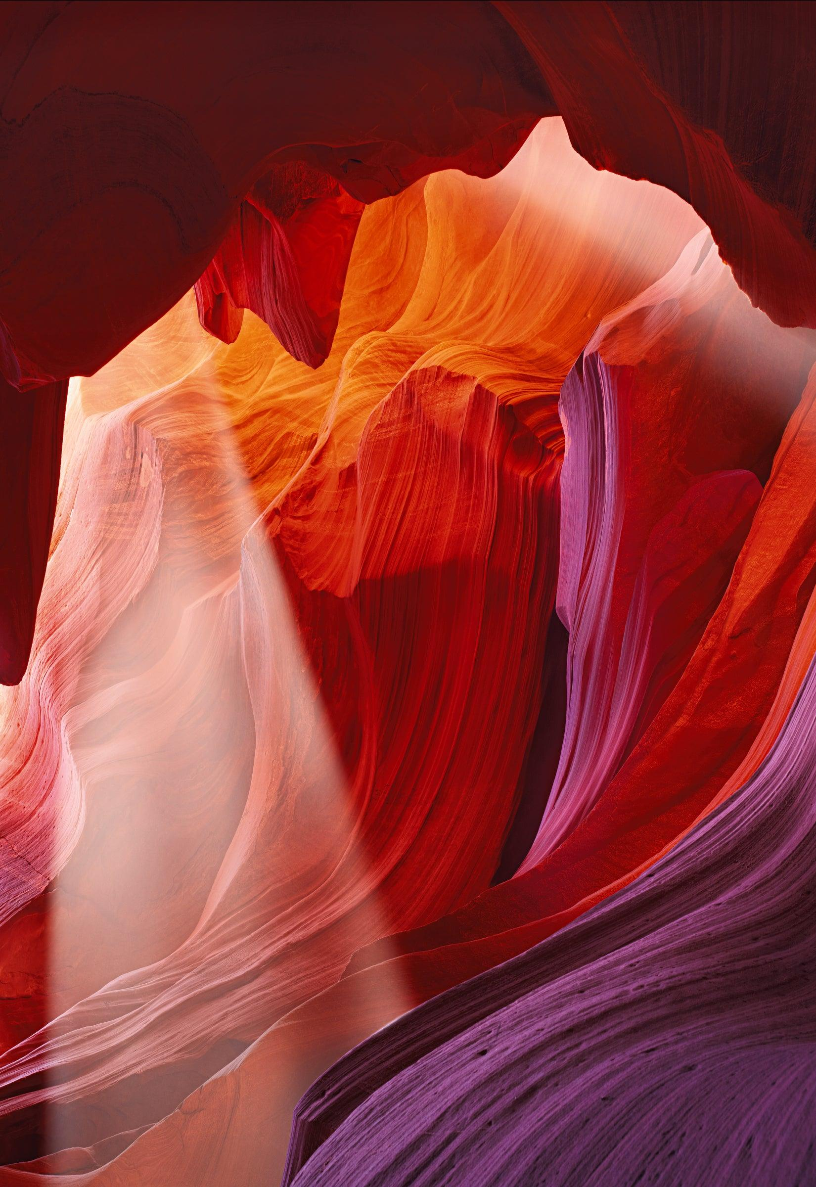 Sun rays shining into the red and pink wave shaped sandstone walls of the slot canyons in Antelope Canyon Arizona