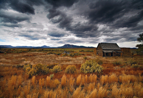 Storm rolling into a brush field with a weathered shack in central Utah