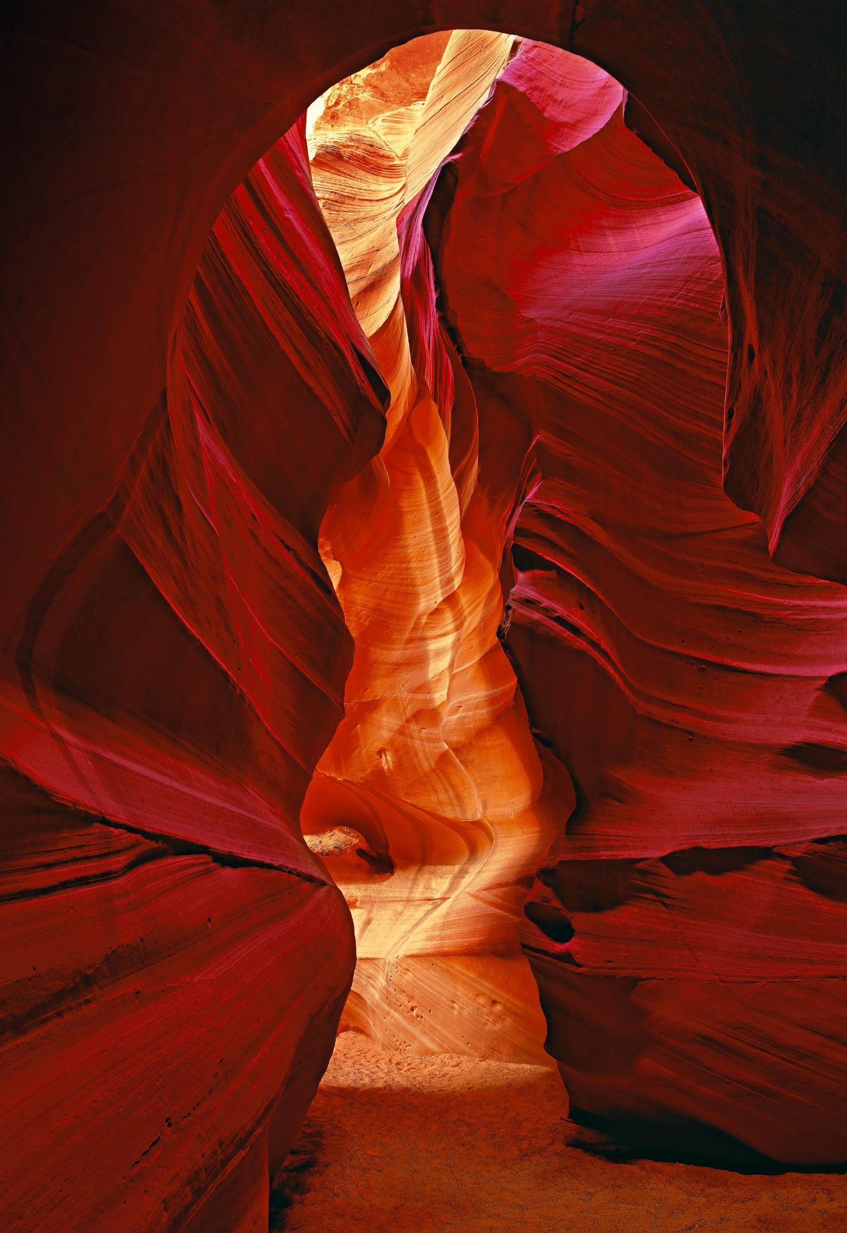 Sand trail leading through red and orange sandstone walls of the slot canyons in Antelope Canyon Arizona