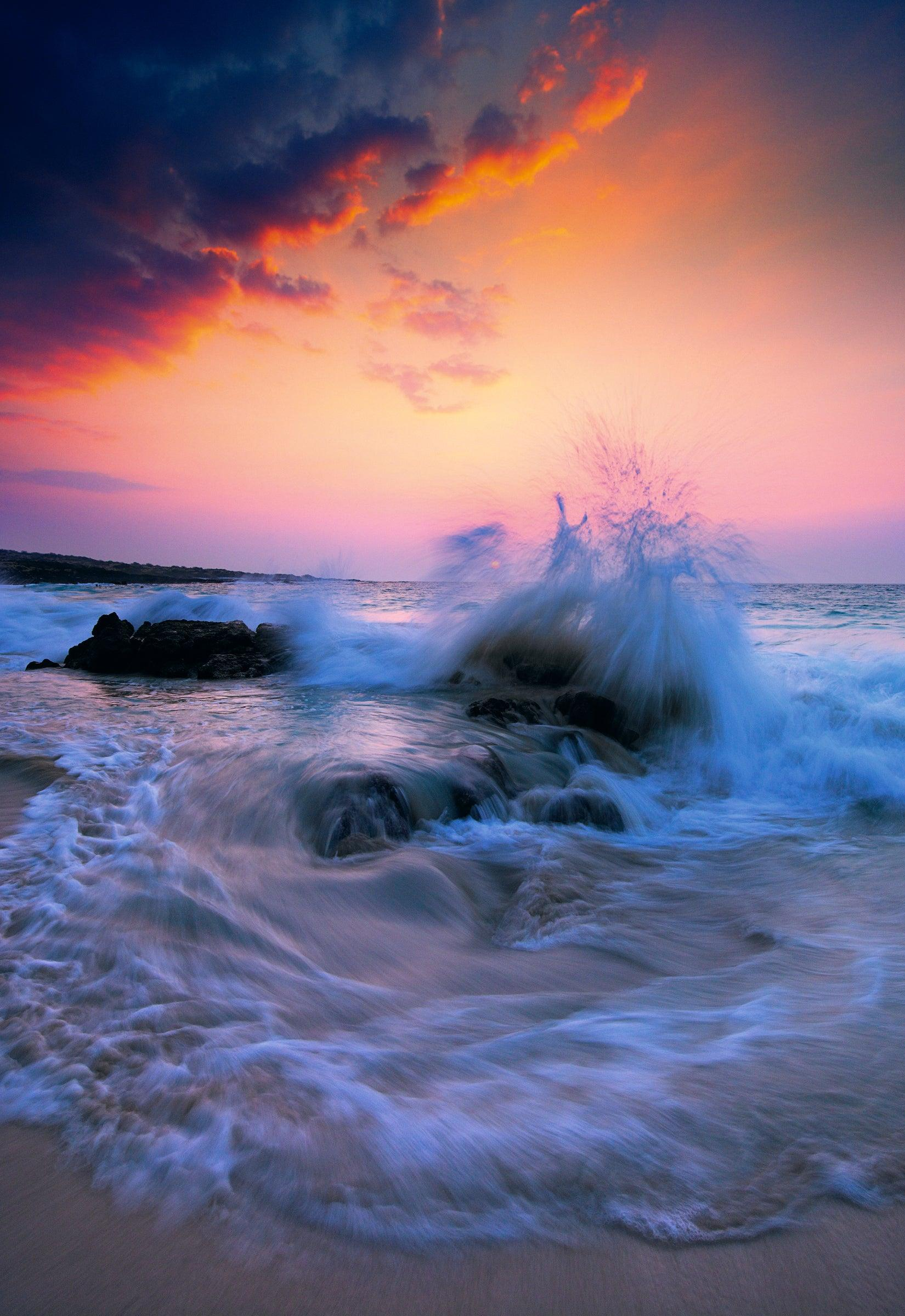 Waves crashing on black rocks on a sand beach on The Big Island Hawaii during a cloudy sunset