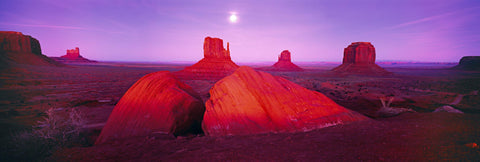 Giant sandstone formations and buttes of Monument Valley Utah during a pink sunset