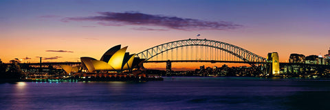 Sydney Harbor Bridge stretching over the harbor to the Sydney Opera House at sunset