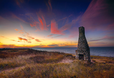 Lone rock fireplace and chimney standing alone on the grass shoreline of Cape Cod Massachusetts