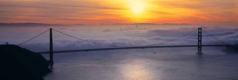 Golden Gate Bridge in front of the fog covered city of San Francisco at sunrise