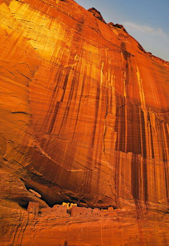 Stone city carved out of the orange cliff face in Canyon de Chelly Ariona