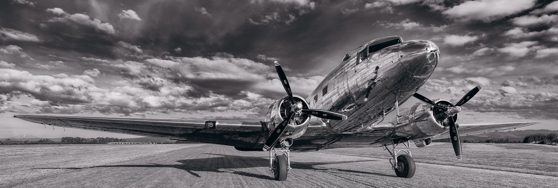 Black and white DC-3 airplane on a grass runway in Portland Oregon under a cloud filled sky