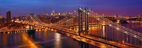 Manhattan Bridge lit up at night overlooking the glow of New York City in the distance
