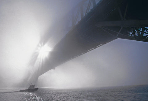 Sun shining through the mist covered Sydney Harbour Bridge Australia with a tug boat driving beneath