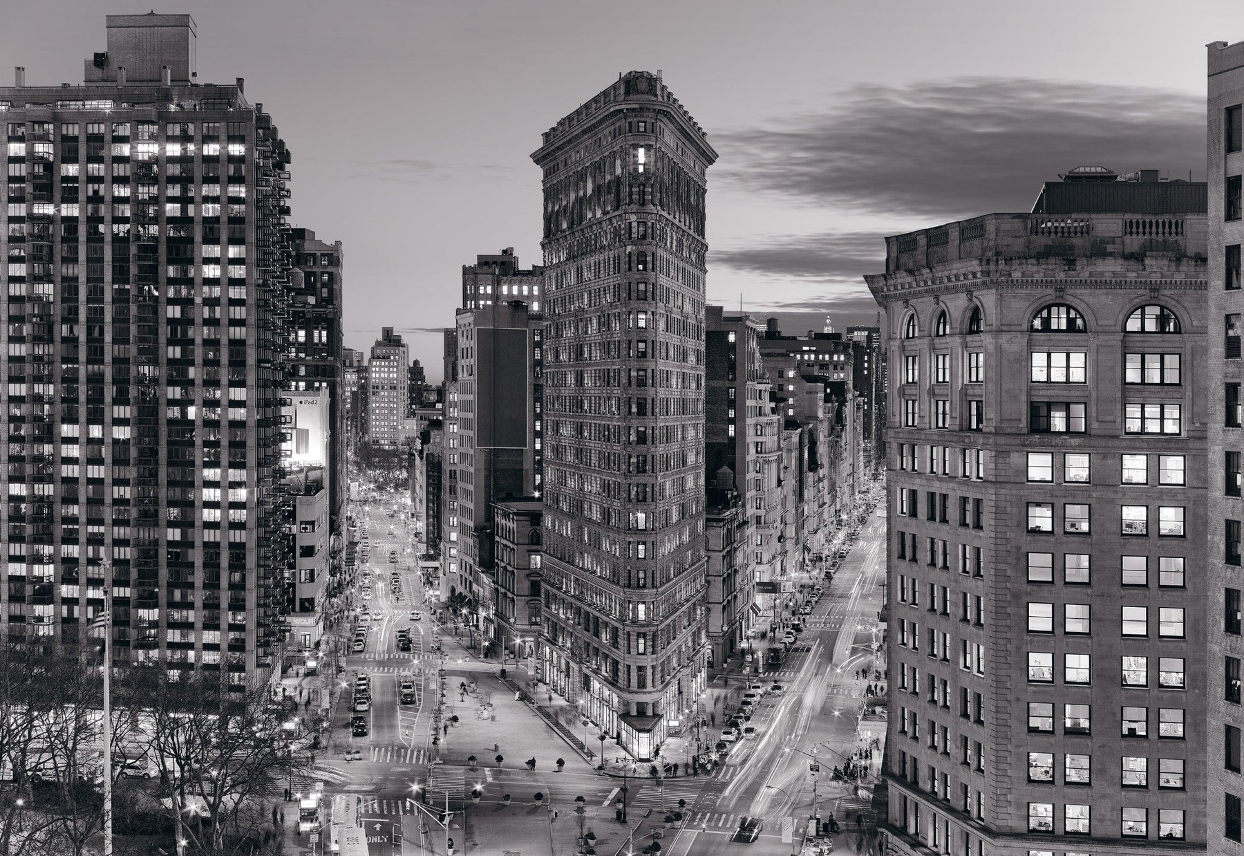 Black and white of the Flat Iron building in New York City and the surrounding streets at dusk