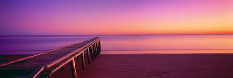 Old timber jetty stretching out over the sand beach of Hervey Bay Australia during a pink sunrise
