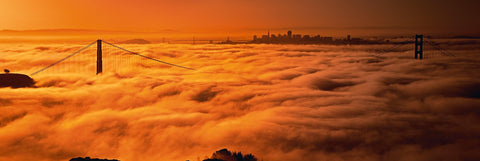 Thick clouds covering the Golden Gate Bridge with the city of San Francisco in the distance during sunrise