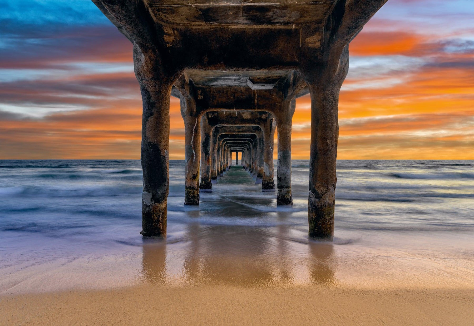 Waves crashing under the pier and onto the sand in Manhattan Beach Calidfornia during a cloudy sunset