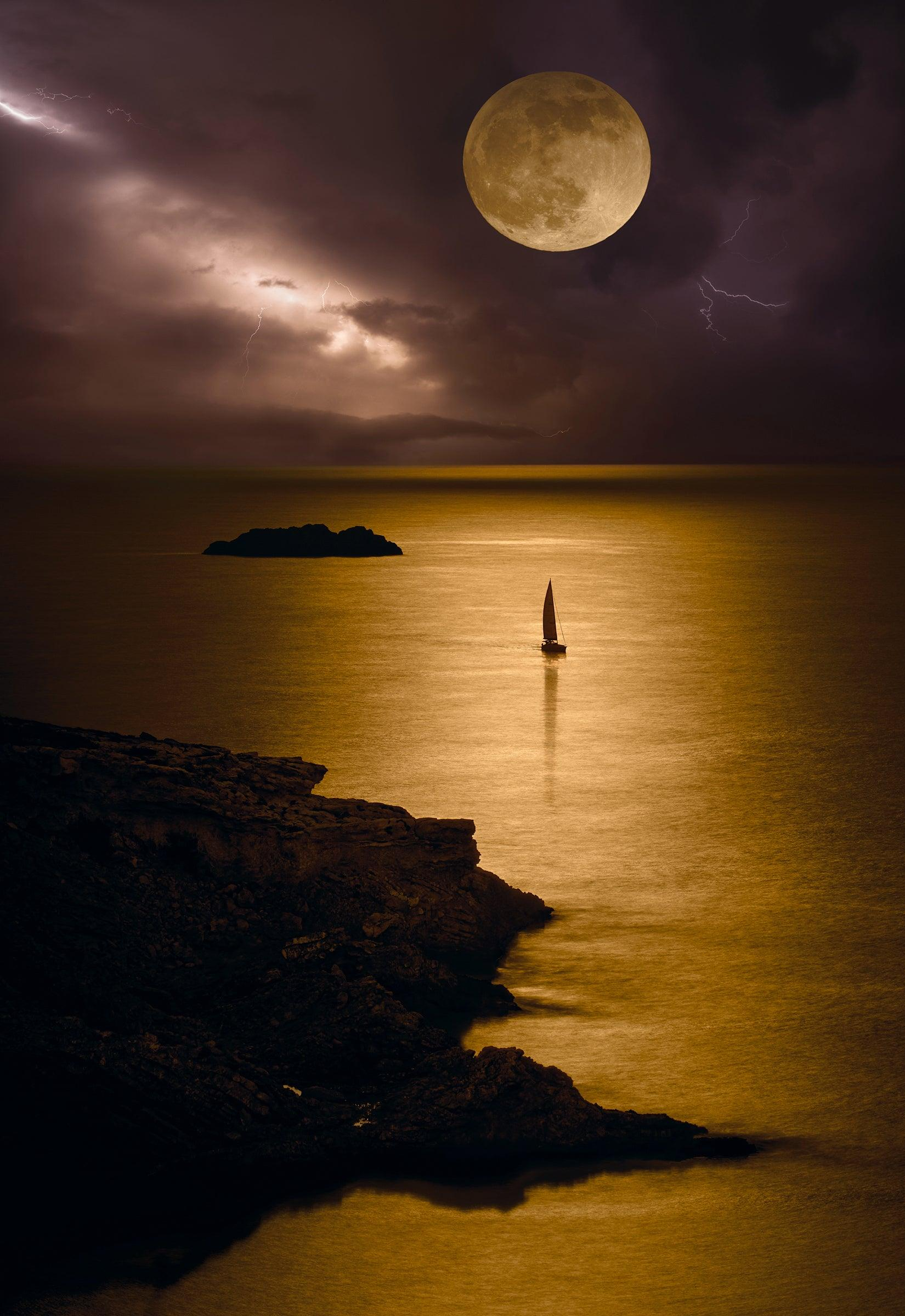Sail boat off the rocky coast of Ibiza, Spain under a full moon and lightning filled sky at night