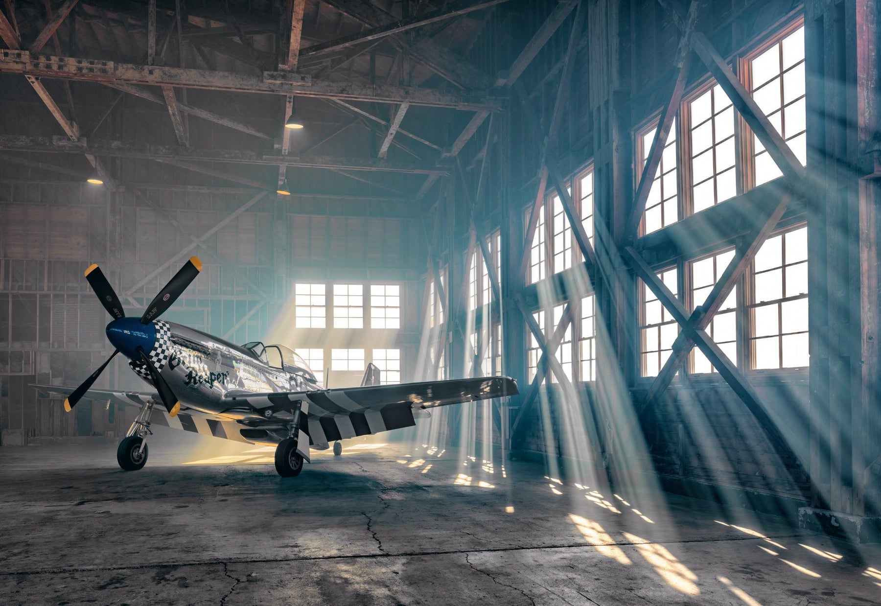 P51 Mustang airplane in the corner of a metal hanger in Aurora Oregon with the sun shining through the windows