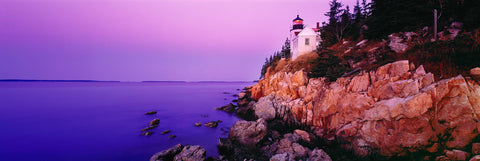 Bass Harbor Head Lighthouse off the edge of a rock cliff and the forest of Acadia National Park during sunrise