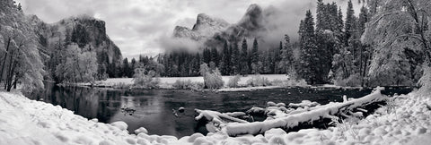 Black and white river running through the snow covered Yosemite Valley with El Capitan mountain in the background