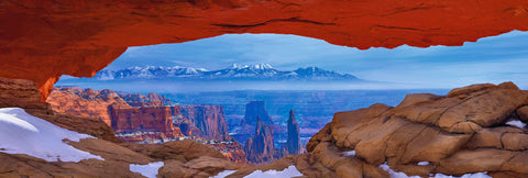 Snow covered rock arch overlooking the buttes and mountains of Canyonlands