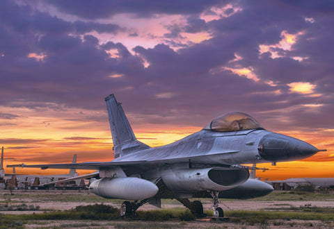 Old F-16 fighter jet sitting on a grass and dirt field in Tucson Arizona at sunset