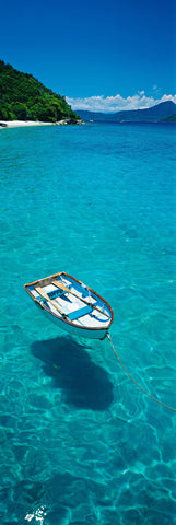 Rowboat floating on the turquoise waters in front of the tree filled Fitzroy Island Australia