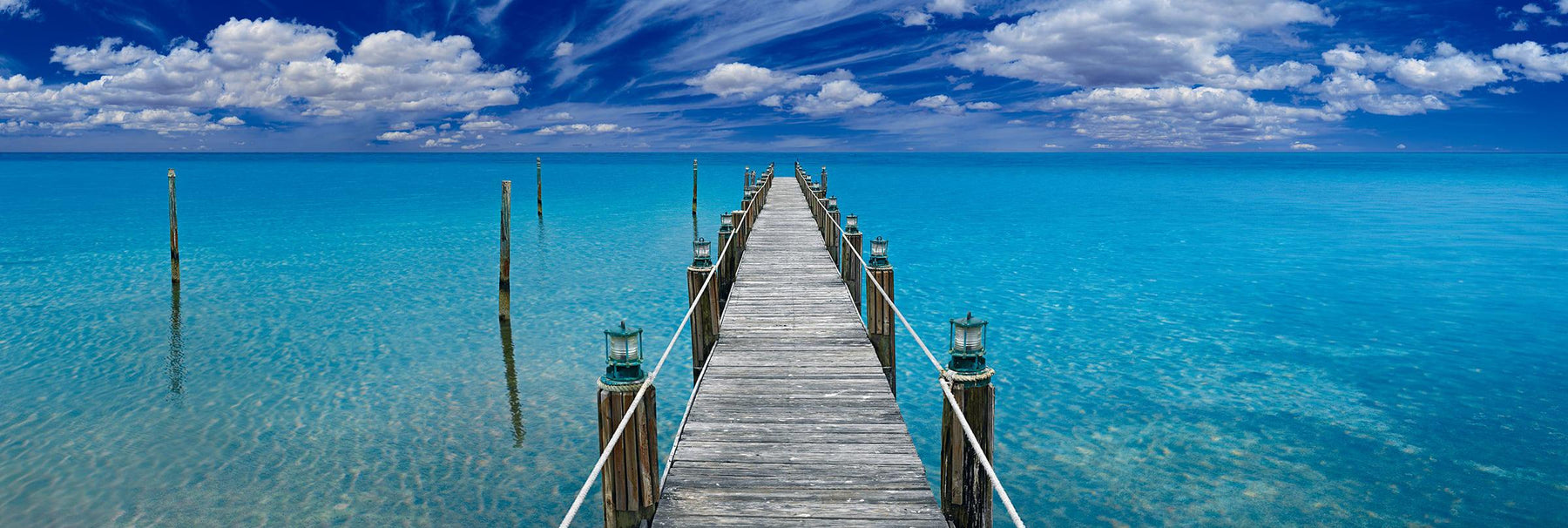 Old wooden jetty with white rope and lanterns leading over a turquoise ocean in Key West Florida