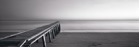 Black and white old wooden jetty leading across the sandy beach and into the ocean in Queensland Australia