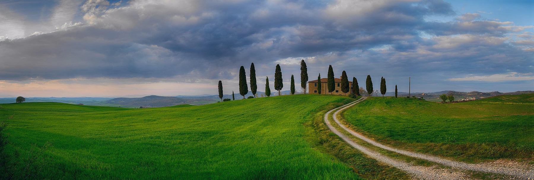 Dirt road leading through a green grass field to a stone house surrounded by cypress trees in Tuscany Italy