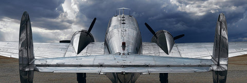 View of silver Beechcraft plane from behind looking into the clouds and blue stormy sky of Tucson Arizona